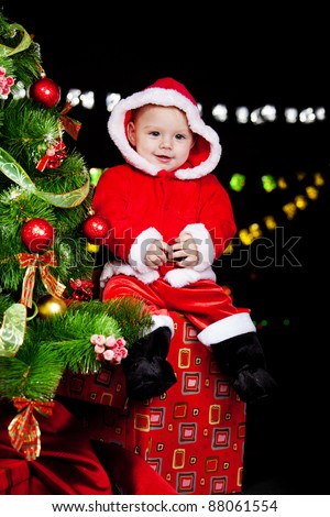 Smiling Santa helper sitting on the Christmas present box - stock photo