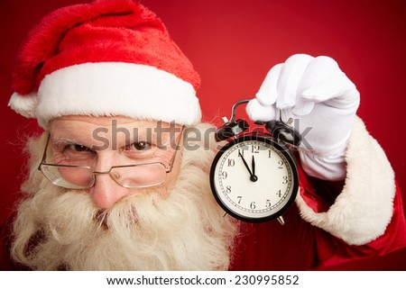 Smiling Santa showing alarm clock with five minutes to twelve - stock photo