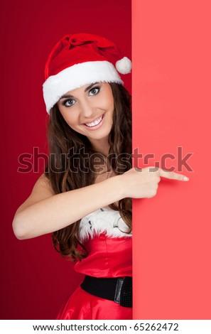 smiling santa woman behind blank board pointing - stock photo