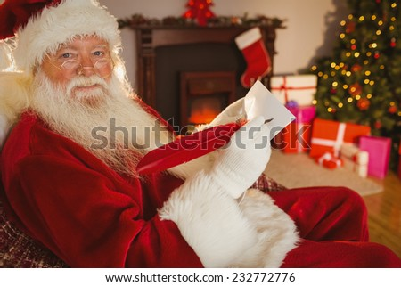 Smiling santa writing list with a quill at home in the living room
