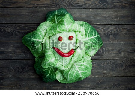 Smiling savoy cabbage on wooden background - stock photo