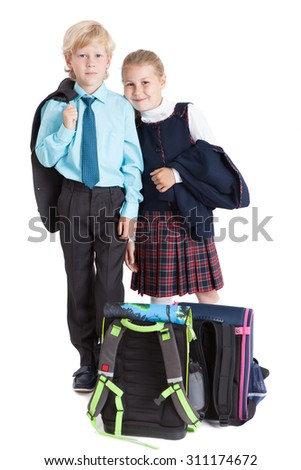 Smiling school children in uniform standing together with schoolbags on the floor, isolated on white background - stock photo