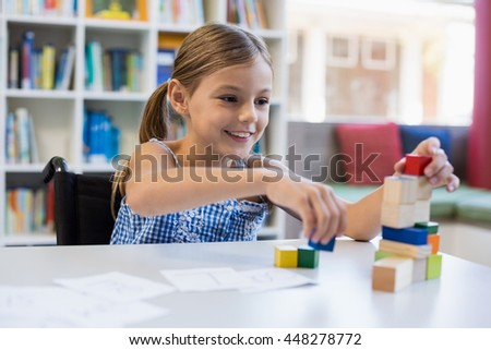 Smiling school girl playing with building block in library at school - stock photo