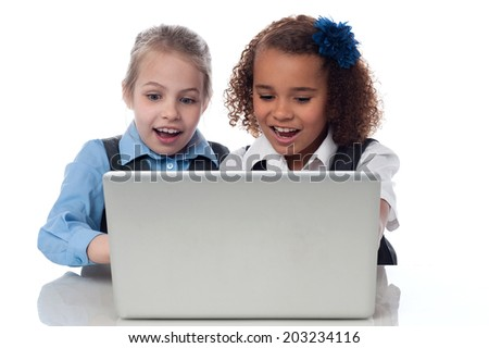 Smiling school girls using laptop together - stock photo
