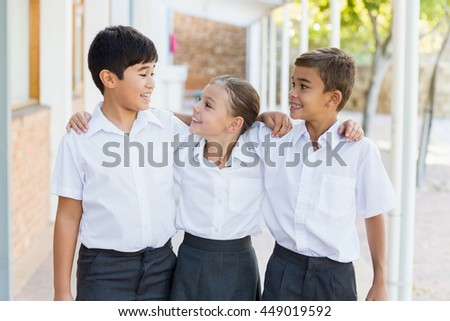 Smiling school kids standing with arm around in corridor at school - stock photo