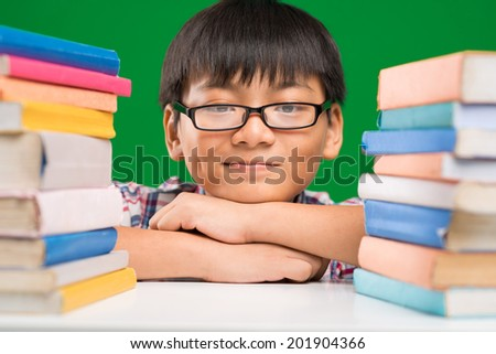 Smiling schoolboy between book stacks - stock photo