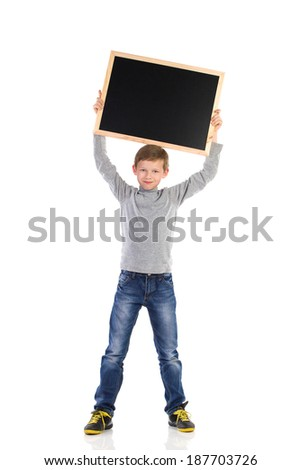 Smiling schoolboy holding blackboard over his head. Full length studio shot isolated on white. - stock photo
