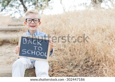 "smiling schoolboy in glasses holding blackboard with ""back to school"" sign ready for school enjoying warm weather in the park - stock photo"