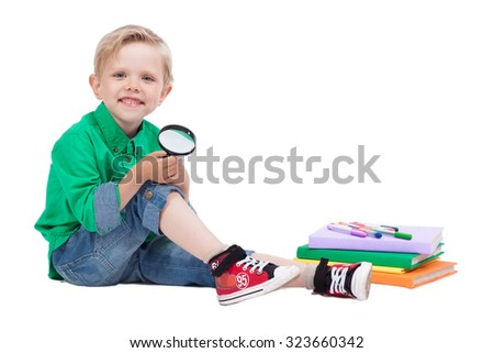 smiling schoolboy sitting on a white background, surrounded by books and holding a magnifying glass, picture with depth of field