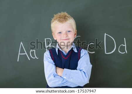 Smiling schoolboy standing at chalkboard and looking at camera. Ffront view. - stock photo