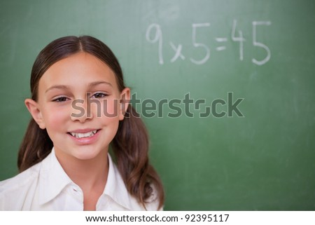 Smiling schoolgirl posing in front of a chalkboard in a classroom - stock photo