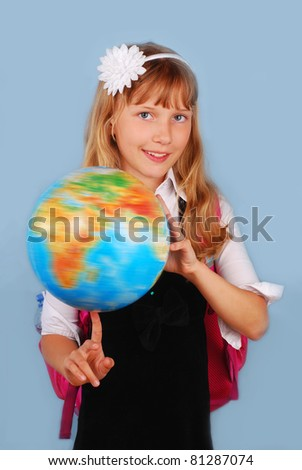 smiling schoolgirl turning the globe on the finger  against blue background - stock photo