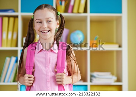 Smiling schoolgirl with backpack looking at camera - stock photo