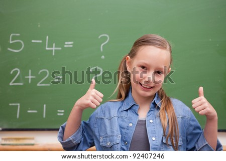 Smiling schoolgirl with the thumbs up in front of a blackboard - stock photo