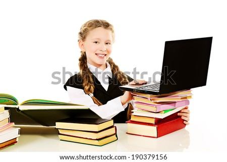 Smiling schoolgirl working with a laptop and textbook. - stock photo