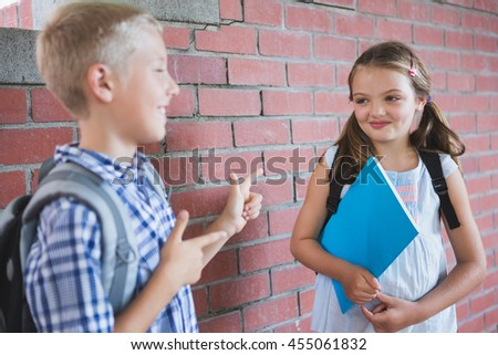 Smiling schoolkids standing in corridor and talking to each other at school - stock photo