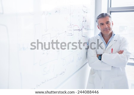 Smiling scientist leaning against the whiteboard in laboratory - stock photo
