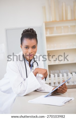 Smiling scientist looking at camera and holding tablet in laboratory - stock photo