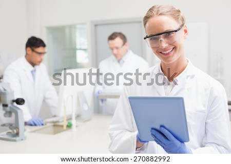Smiling scientist using tablet while colleagues working behind in laboratory - stock photo