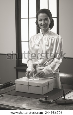 Smiling secretary holding a mail package with rope and label, 1950s style
