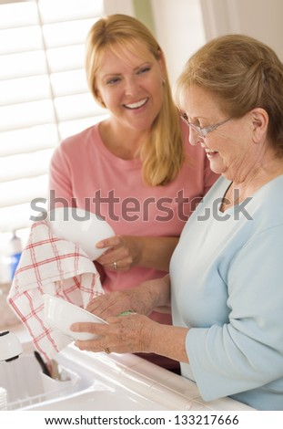 Smiling Senior Adult Woman and Young Daughter Talking At Sink in Kitchen.