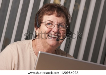 Smiling Senior Adult Woman with Telephone Headset In Front of Computer Monitor. - stock photo
