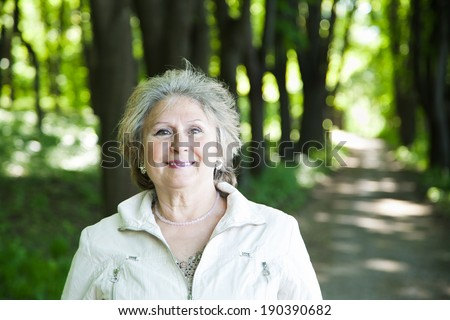 smiling senior aged woman outdoors in forest with copy space - stock photo