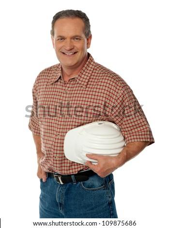 Smiling senior architect holding white safety hat posing casually - stock photo