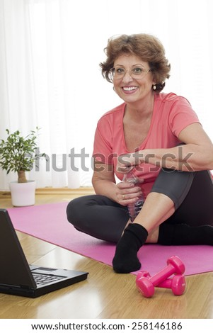 Smiling senior brown haired woman  sitting on the parquet floor holding a bottle of water and looking at camera. - stock photo