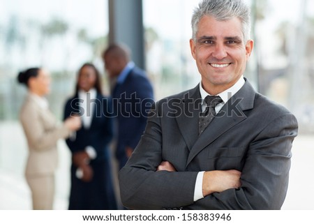 smiling senior business executive with arms folded in office - stock photo
