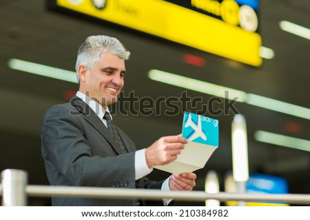 smiling senior businessman looking at his air ticket at airport - stock photo