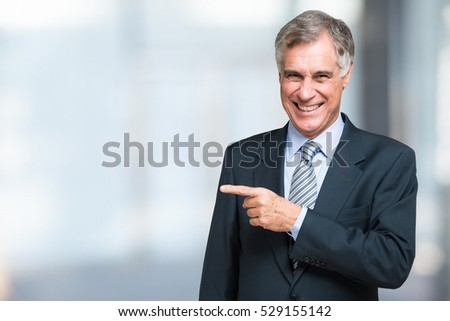Smiling senior businessman pointing his finger on the white space