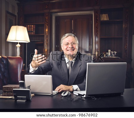 Smiling senior businessman welcoming in his office - stock photo