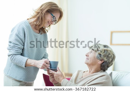 Smiling senior care assistant helping elderly lady - stock photo
