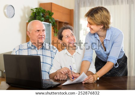 Smiling senior couple answer questions of social worker at home. Focus on woman
