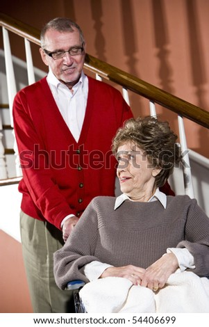 Smiling senior couple at home, woman in wheelchair - stock photo