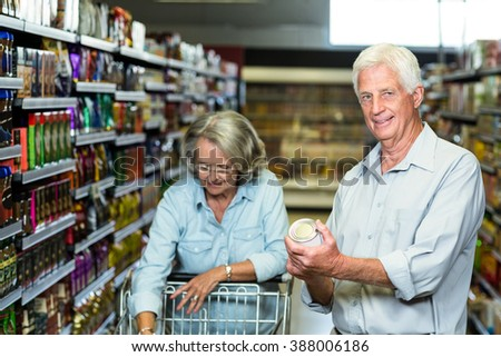 Smiling senior couple buying food at the supermarket