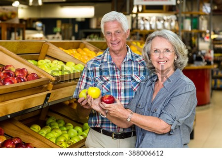 Smiling senior couple holding apples at the grocery shop