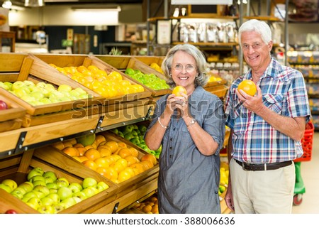 Smiling senior couple holding oranges at the grocery shop - stock photo