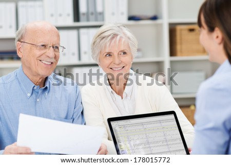 Smiling senior couple meeting with a broker in her office sitting close together holding paperwork and listening to her speak - stock photo