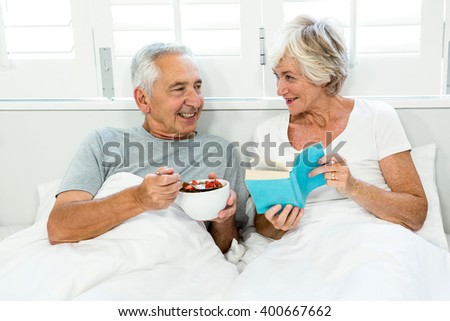 Smiling senior couple relaxing on bed at home - stock photo
