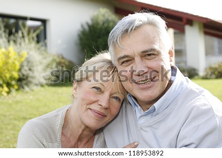 Smiling senior couple sitting in garden - stock photo