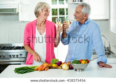 Smiling senior couple toasting white wine while preparing vegetables in kitchen - stock photo