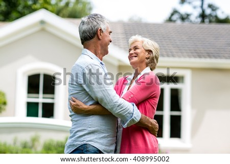 Smiling senior couple with arms around against house at yard - stock photo