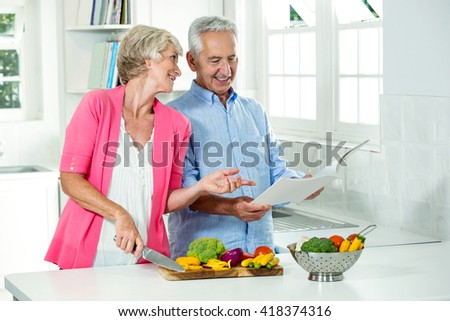 Smiling senior couple with recipe book while preparing vegetables in kitchen - stock photo