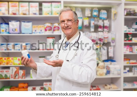 Smiling senior doctor showing medication in the pharmacy - stock photo