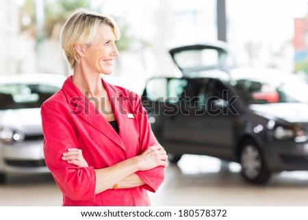 smiling senior female car dealer principal looking away - stock photo
