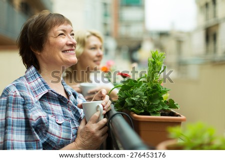 Smiling senior female friends staying on balcony with cup of coffee in hands - stock photo