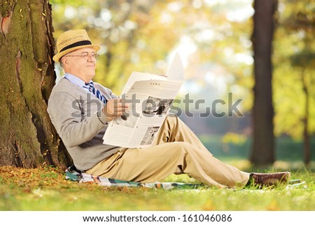 Smiling senior gentleman seated on a grass reading a newspaper in a park at autumn - stock photo