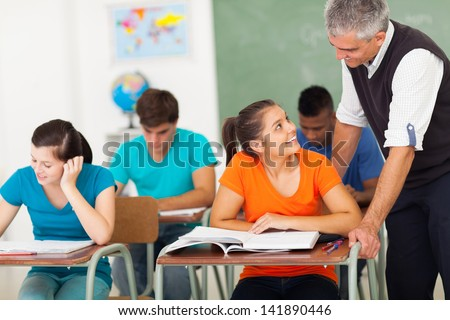 smiling senior high school teacher talking to student in classroom - stock photo